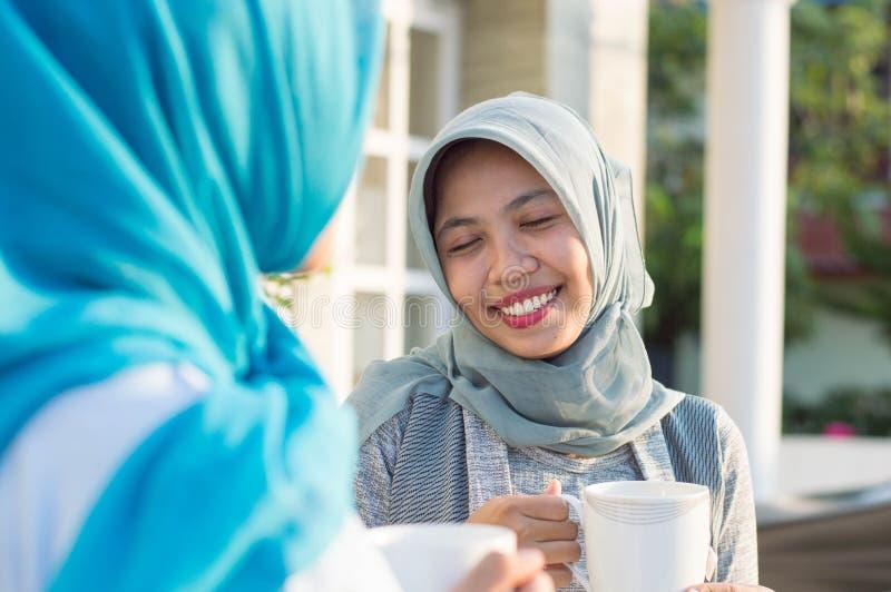 Κλείστε επάνω τις ευτυχείς βλασταημένες δύο γυναίκες hijab που πίνουν το τσάι μπροστά από το σπίτι και το χαμόγελο στοκ φωτογραφία με δικαίωμα ελεύθερης χρήσης