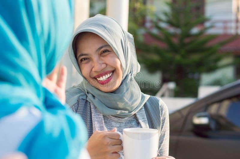 Κλείστε επάνω τις ευτυχείς βλασταημένες δύο γυναίκες hijab που πίνουν το τσάι μπροστά από το σπίτι και το χαμόγελο στοκ εικόνα με δικαίωμα ελεύθερης χρήσης