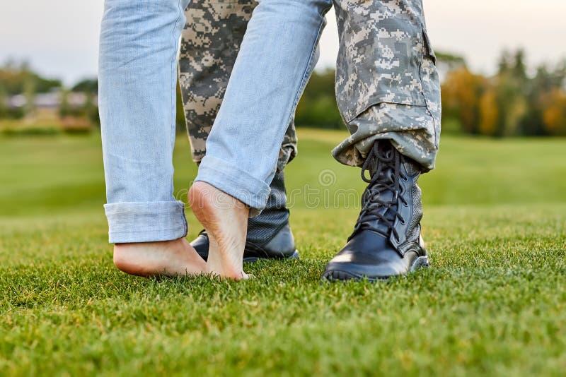 Κλείστε επάνω τις μπότες και τη φίλη στρατιωτών με τα γυμνά πόδια στοκ εικόνες με δικαίωμα ελεύθερης χρήσης