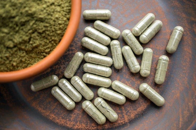 Κλείστε επάνω τις πράσινες κάψες και τη σκόνη σε ένα καφετί πιάτο αργίλου σε ένα Bu στοκ εικόνα με δικαίωμα ελεύθερης χρήσης