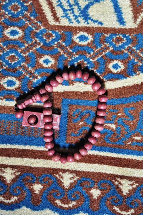 Κλείστε επάνω τις χάντρες προσευχής που απομονώνονται στην κουβέρτα προσευχής στοκ φωτογραφίες