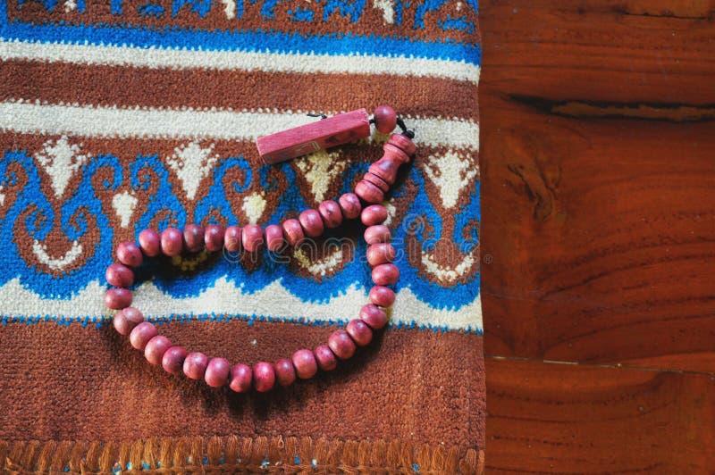 Κλείστε επάνω τις χάντρες προσευχής στην κουβέρτα προσευχής στοκ εικόνα