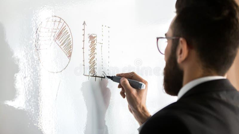 Κλείστε επάνω τον επιχειρηματία που φορά τα γυαλιά επισύροντας την προσοχή τις γραφικές παραστάσεις στο διάγραμμα κτυπήματος στοκ φωτογραφίες με δικαίωμα ελεύθερης χρήσης