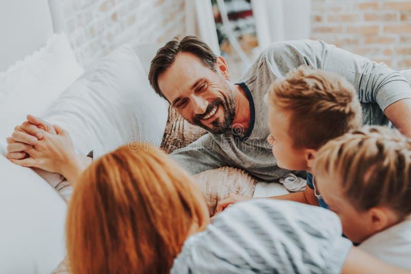 Κλείστε επάνω τον ευτυχή πατέρα με την οικογένειά του στο κρεβάτι στοκ φωτογραφίες