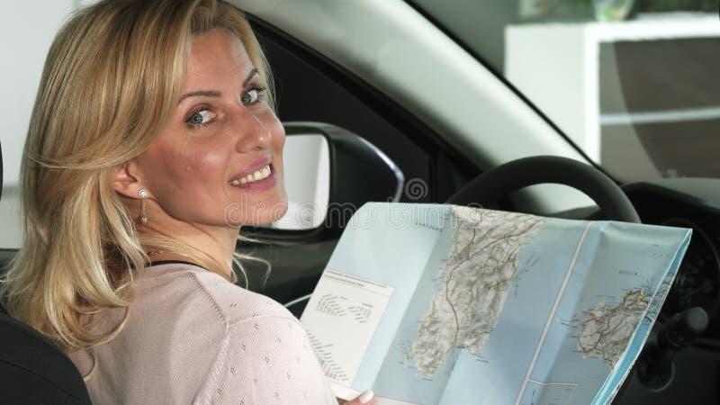 Κλείστε επάνω τον οπισθοσκόπο πυροβολισμό ενός θηλυκού οδηγού χρησιμοποιώντας έναν χάρτη στο αυτοκίνητό της στοκ φωτογραφία με δικαίωμα ελεύθερης χρήσης