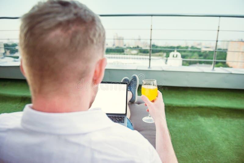 Κλείστε επάνω τον πίσω επιχειρηματία άποψης με το ποτό που λειτουργεί άνετα στο lap-top με την άσπρη κενή συνεδρίαση οθόνης στο π στοκ φωτογραφία
