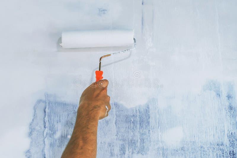 κλείστε επάνω τον τοίχο ζωγραφικής χεριών με τον κύλινδρο στοκ εικόνες με δικαίωμα ελεύθερης χρήσης