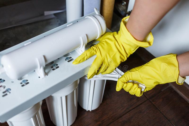 Κλείστε επάνω τον υδραυλικό στα κίτρινα φίλτρα νερού αλλαγών οικιακών γαντιών Μεταβαλλόμενες κασέτες φίλτρων νερού επισκευαστών σ στοκ εικόνα