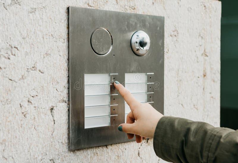 Κλείστε επάνω τους θηλυκούς Τύπους χεριών το κουμπί doorphone Το κορίτσι καλεί την ενδοσυνεννόηση στοκ φωτογραφία με δικαίωμα ελεύθερης χρήσης