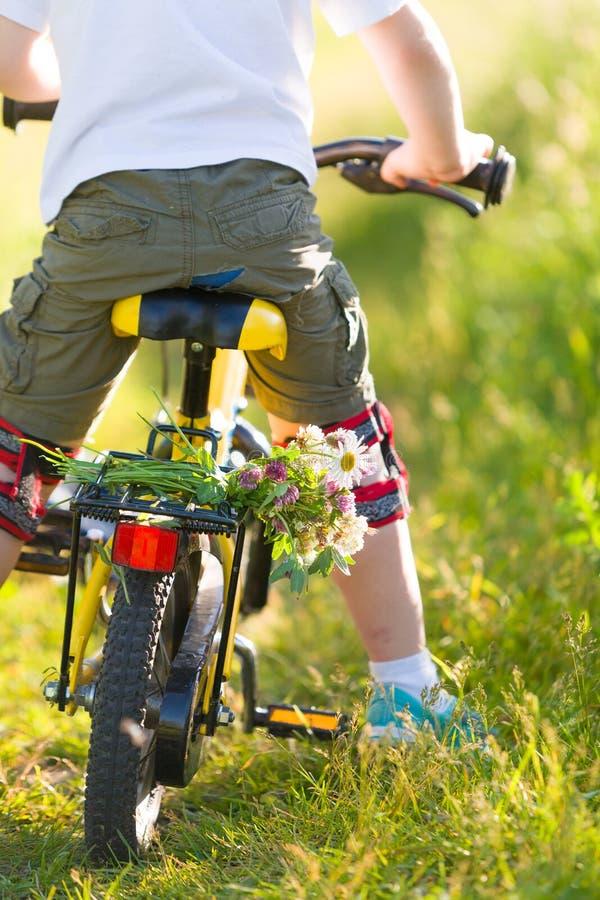 Κλείστε επάνω του αγοριού παιδάκι που οδηγά στο ποδήλατό του με τα λουλούδια, υπαίθρια Αγόρι που οδηγά το πρώτο κίτρινο ποδήλατό  στοκ εικόνες