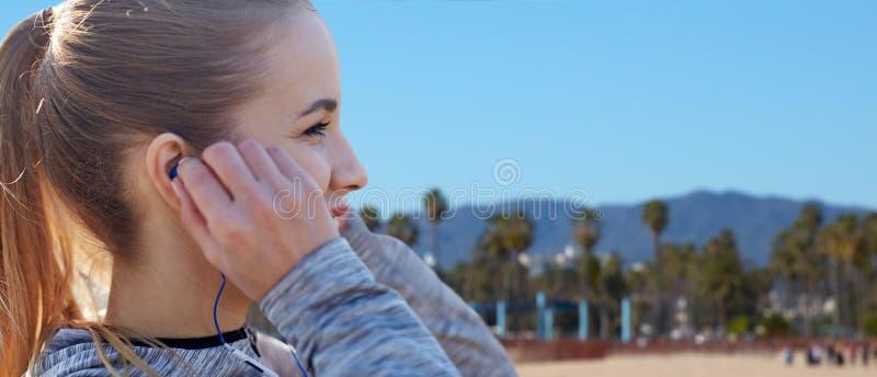 Κλείστε επάνω του ακούσματος γυναικών στη μουσική στα ακουστικά στοκ εικόνα με δικαίωμα ελεύθερης χρήσης