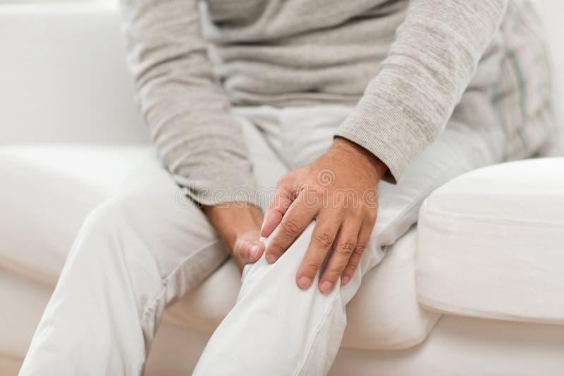 Κλείστε επάνω του ανώτερου ατόμου που πάσχει από τον πόνο γονάτων στοκ εικόνα