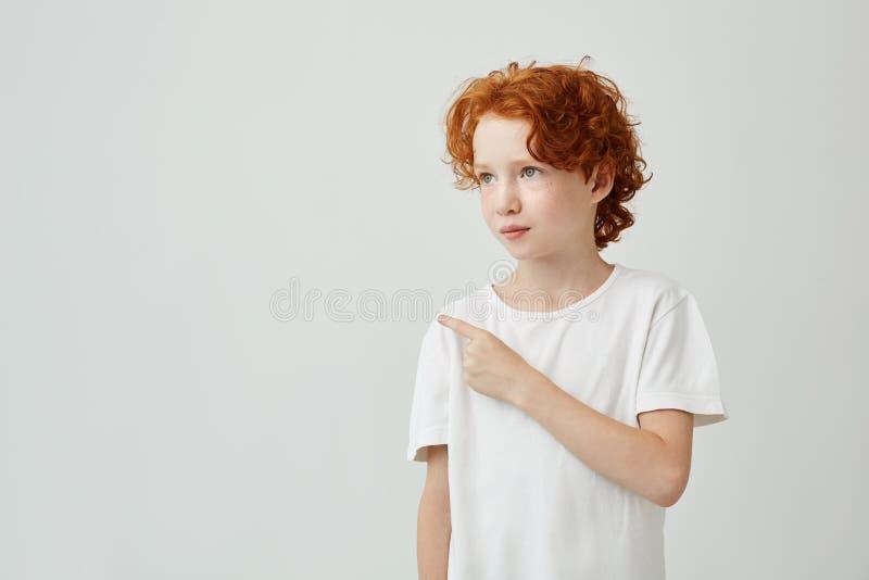 Κλείστε επάνω του αρκετά σγουρού redhead αγοριού με τις φακίδες στην άσπρη μπλούζα που εξετάζει κατά μέρος, που δείχνει τον άσπρο στοκ φωτογραφία με δικαίωμα ελεύθερης χρήσης