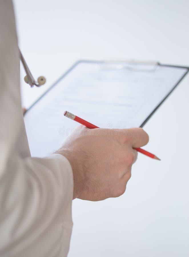 Κλείστε επάνω του αρσενικού γιατρού χεριών που γεμίζει την ιατρική μορφή Κινηματογράφηση σε πρώτο πλάνο του αρσενικού γιατρού που στοκ εικόνα
