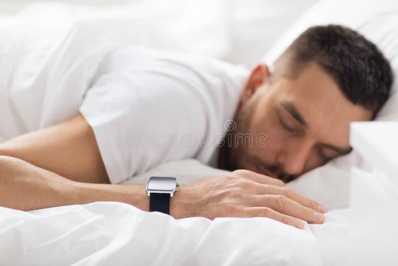 Κλείστε επάνω του ατόμου με τον έξυπνο ύπνο ρολογιών στο κρεβάτι στοκ φωτογραφίες με δικαίωμα ελεύθερης χρήσης