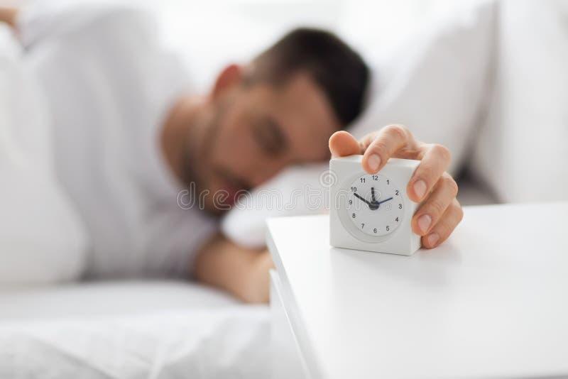 Κλείστε επάνω του ατόμου στο κρεβάτι που φθάνει για το ξυπνητήρι στοκ εικόνα