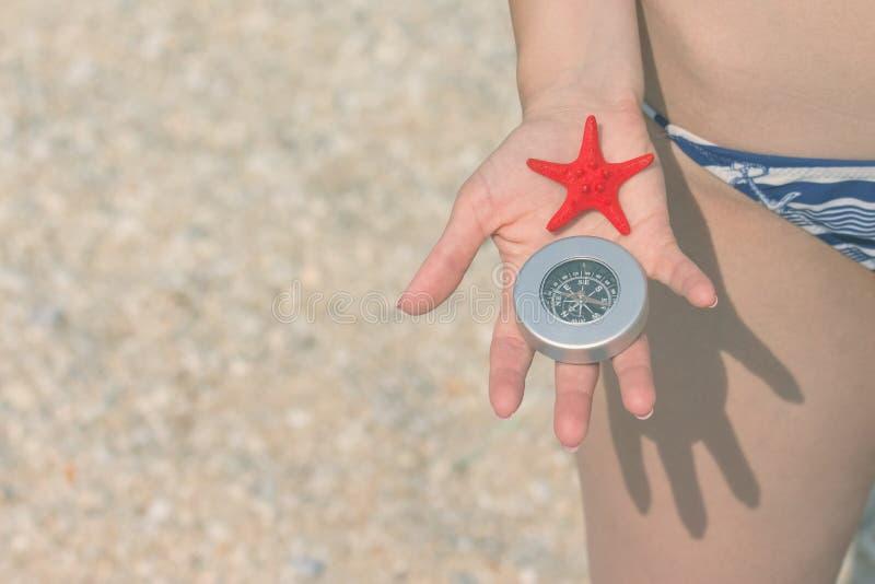 Κλείστε επάνω του θηλυκών αστερία και της πυξίδας εκμετάλλευσης χεριών στο beac στοκ εικόνα