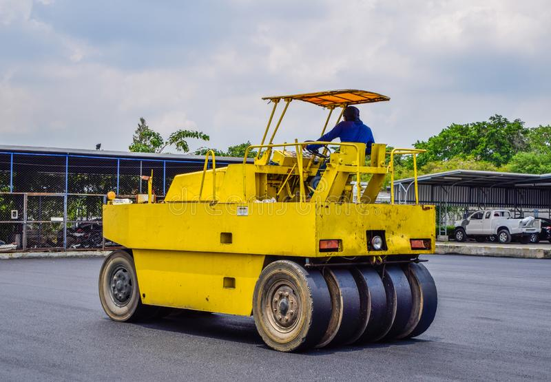 Κλείστε επάνω του κίτρινου οδικού κυλίνδρου, οι άνδρες εργαζόμενοι οδηγούν έναν δρόμο στοκ φωτογραφίες με δικαίωμα ελεύθερης χρήσης