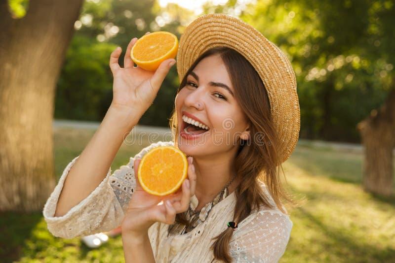 Κλείστε επάνω του καλού νέου κοριτσιού στο χρόνο εξόδων θερινών καπέλων στο πάρκο, στοκ εικόνες