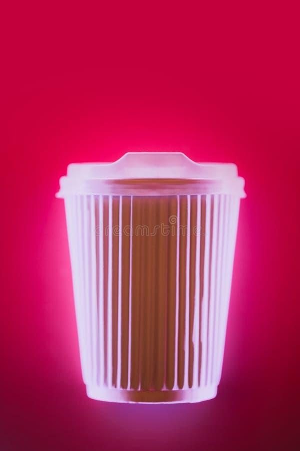 Κλείστε επάνω του καφέ για να πάτε φλυτζάνι στο φως νέου στο φωτεινό ρόδινο υπόβαθρο στοκ φωτογραφία με δικαίωμα ελεύθερης χρήσης