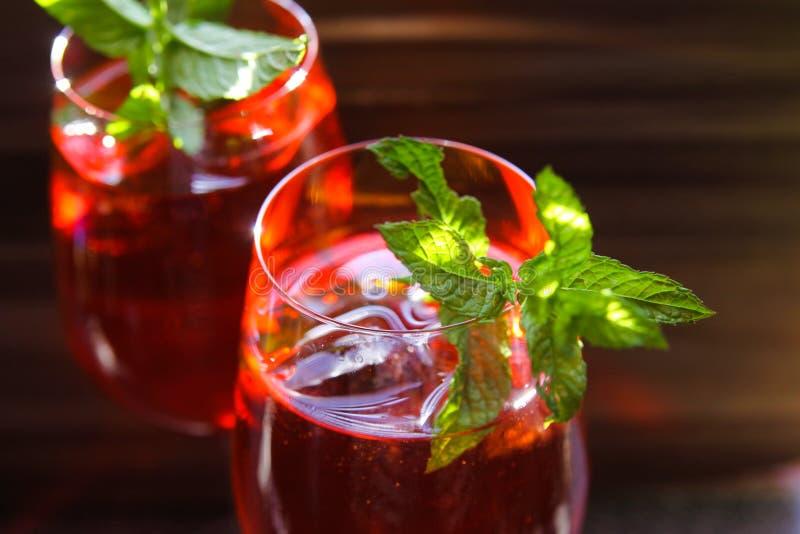 Κλείστε επάνω του κόκκινου κοκτέιλ με τα πράσινα φύλλα μεντών κύβων πάγου στο γυαλί κρασιού στοκ φωτογραφία