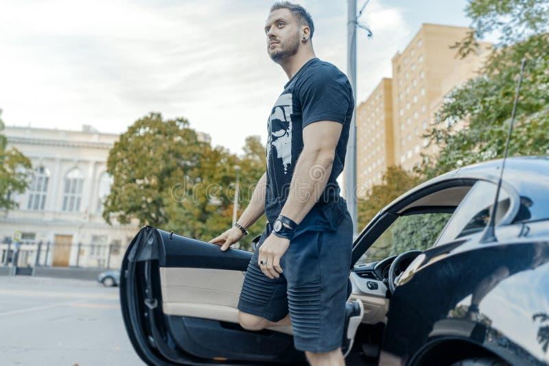 Κλείστε επάνω του νέου ελκυστικού ατόμου που ξεπερνά το μαύρο αυτοκίνητο Πλάγια όψη στοκ φωτογραφία με δικαίωμα ελεύθερης χρήσης