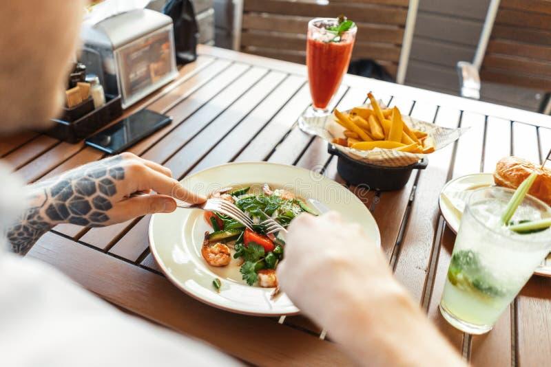 Κλείστε επάνω του νέου ελκυστικού ατόμου που τρώει τη σαλάτα στον καφέ οδών υποστηρίξτε την όψη στοκ εικόνες