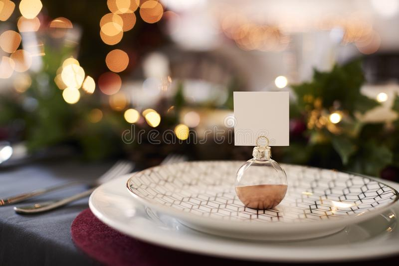 Κλείστε επάνω του πίνακα Χριστουγέννων θέτοντας με τον κάτοχο καρτών ονόματος μπιχλιμπιδιών που τακτοποιείται σε ένα πιάτο και πρ στοκ εικόνα