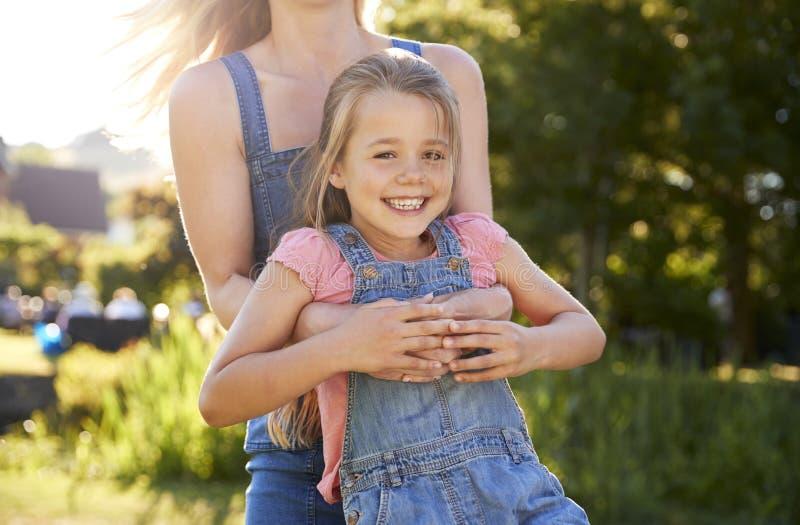 Κλείστε επάνω του παίζοντας παιχνιδιού μητέρων και της ταλαντεμένος κόρης γύρω στον κήπο του θερινού μπαρ στοκ φωτογραφία με δικαίωμα ελεύθερης χρήσης
