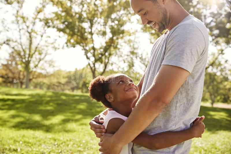 Κλείστε επάνω του πατέρα που αγκαλιάζει την κόρη στο πάρκο στοκ εικόνες
