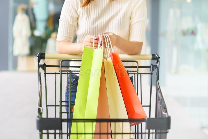 Κλείστε επάνω του πελάτη γυναικών που κρατά τις ζωηρόχρωμες τσάντες αγορών εγγράφου στοκ φωτογραφίες