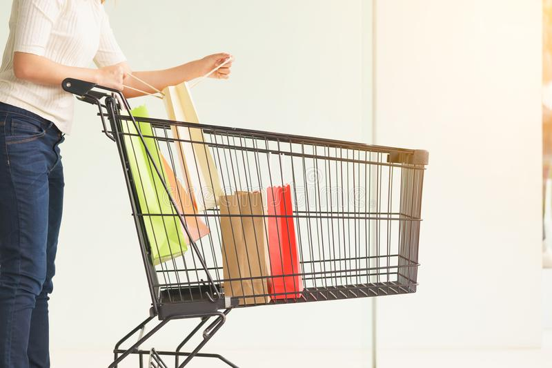Κλείστε επάνω του πελάτη γυναικών που κρατά τις ζωηρόχρωμες τσάντες αγορών εγγράφου στοκ εικόνες
