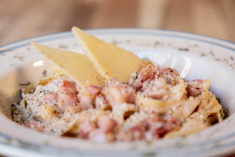 Κλείστε επάνω του πιάτου μακαρονιών Carbonara σε έναν ξύλινο πίνακα με το τυρί, το μπέϊκον και το πιπέρι στοκ εικόνες