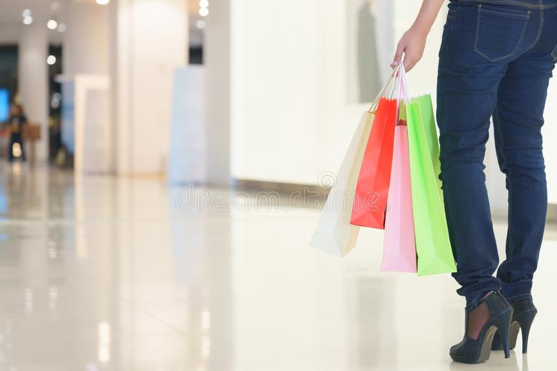Κλείστε επάνω του ποδιού πελατών γυναικών με τις ζωηρόχρωμες τσάντες αγορών εγγράφου στοκ εικόνες