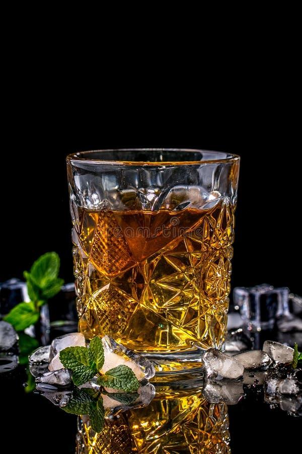 Κλείστε επάνω του ποτηριού κρυστάλλου του ουίσκυ, του κονιάκ ή σκωτσέζικος, του πάγου και της φρέσκιας μέντας στο μαύρο υπόβαθρο, στοκ φωτογραφία