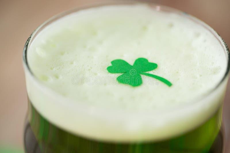 Κλείστε επάνω του ποτηριού της πράσινης μπύρας με το τριφύλλι στοκ εικόνα με δικαίωμα ελεύθερης χρήσης