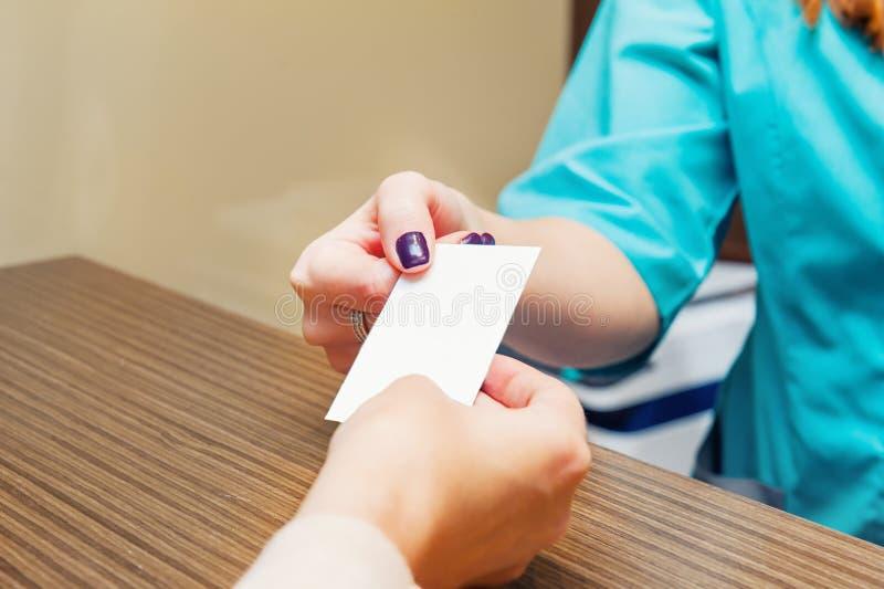 Κλείστε επάνω του ρεσεψιονίστ δίνει την κάρτα επίσκεψης με το κενό κενό στο θηλυκό ασθενή στην ιατρική κλινική Εκλεκτική εστίαση, στοκ φωτογραφίες με δικαίωμα ελεύθερης χρήσης
