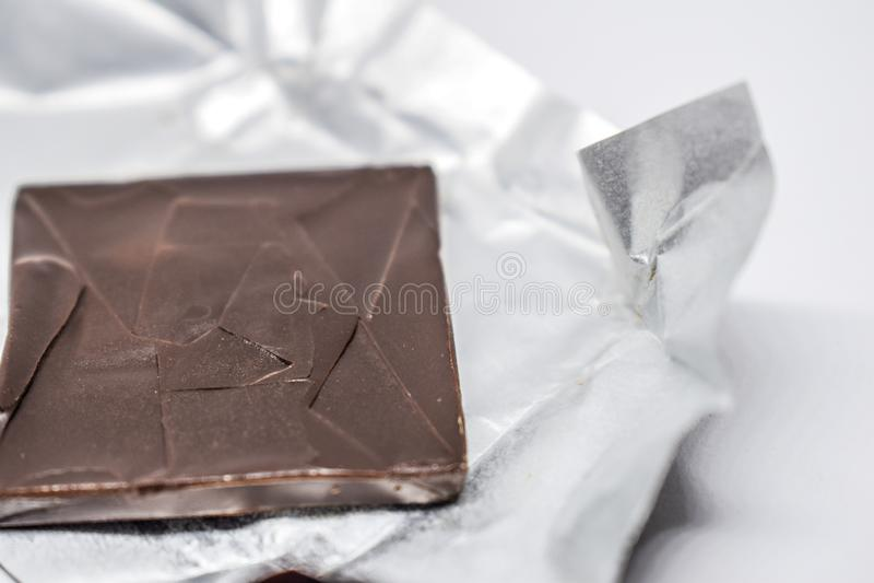 Κλείστε επάνω του σκοτεινού καφετιού τετραγώνου σοκολάτας που ραγίζεται στο ασημένιο φύλλο αλουμινίου σε ένα άσπρο υπόβαθρο στοκ εικόνες με δικαίωμα ελεύθερης χρήσης
