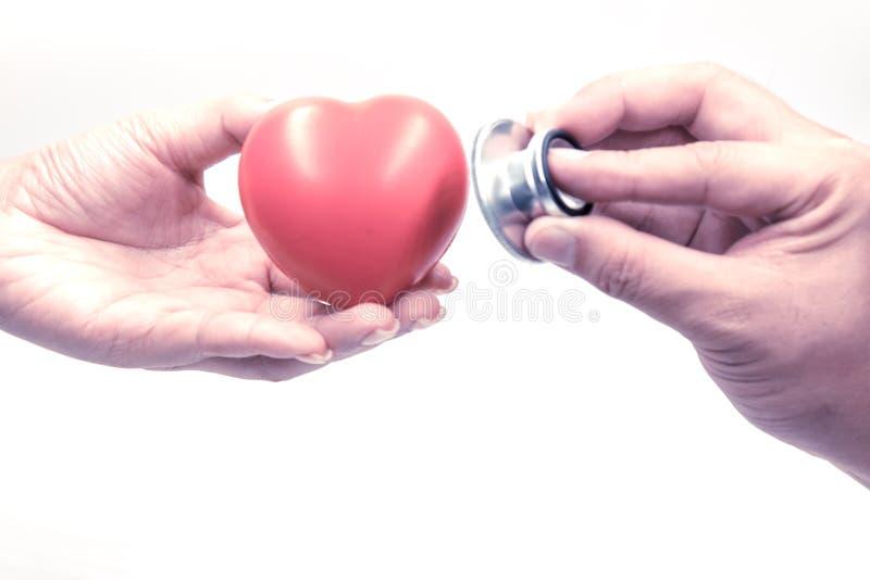 Κλείστε επάνω του στηθοσκοπίου εκμετάλλευσης ανδρών και έλεγχος της καρδιάς στο χέρι γυναικών στοκ εικόνες