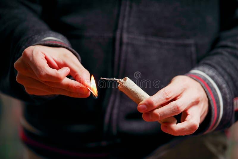 Κλείστε επάνω του φωτισμού χεριών ατόμων επάνω firecrackers σε ένα σαλιασμένο υπόβαθρο στοκ εικόνα