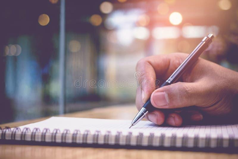 Κλείστε επάνω του χεριού ατόμων ένα βιβλίο κειμένων εργασίας γραψίματος μανδρών στη βιβλιοθήκη η εκπαίδευση έννοιας βιβλίων απομό στοκ φωτογραφία