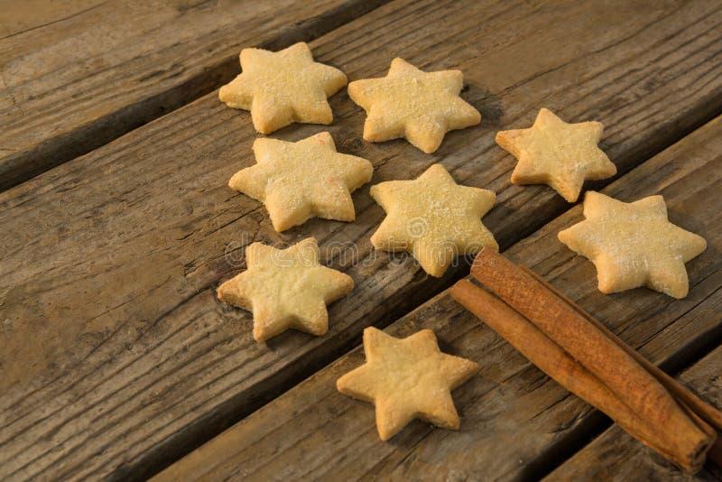 Κλείστε επάνω του χριστουγεννιάτικου δέντρου που γίνεται με το μπισκότο μορφής αστεριών και το ραβδί κανέλας στοκ φωτογραφία