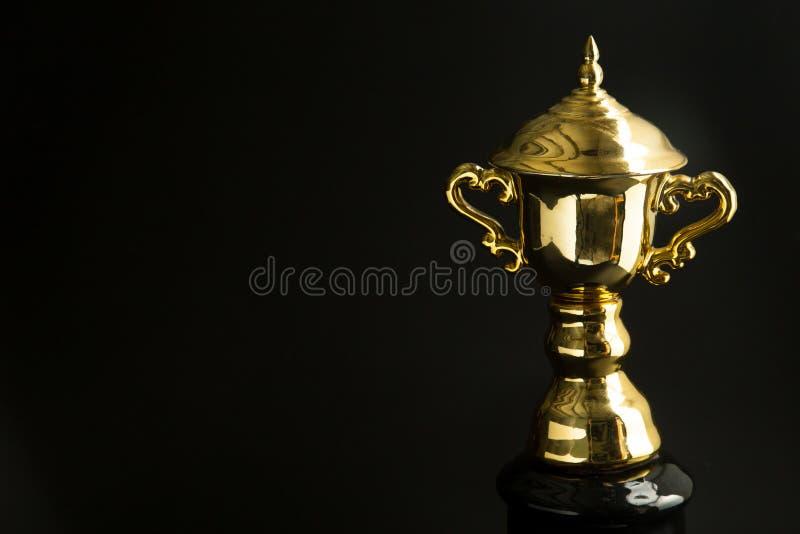 Κλείστε επάνω του χρυσού τροπαίου πέρα από το μαύρο υπόβαθρο Κερδίζοντας βραβεία με το διάστημα αντιγράφων για το κείμενο και το  στοκ εικόνα
