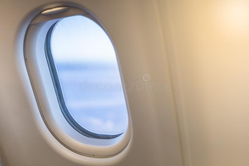 Κλείστε επάνω του ωοειδούς παραθύρου αεροπλάνων με το μπλε ουρανό έννοια μεταφορών και ταξιδιού στοκ εικόνα με δικαίωμα ελεύθερης χρήσης