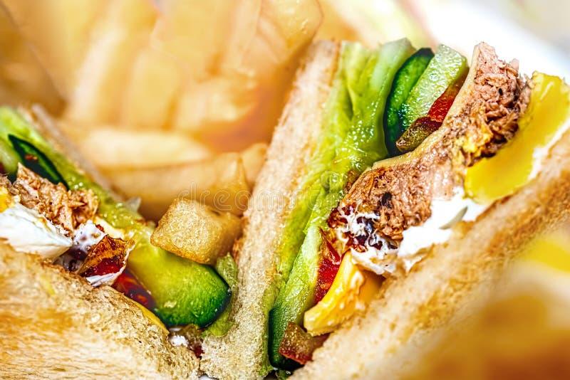 Κλείστε επάνω του Juicy σάντουιτς λεσχών με Lectuce και των τουρσιών με τις τηγανιτές πατάτες θαμπάδων στο υπόβαθρο στοκ εικόνες