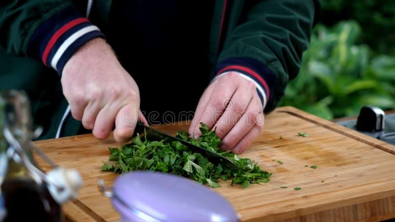Κλείστε επάνω το άτομο μαγειρεύει τον ξύλινο πίνακα μαϊντανού στοκ εικόνα