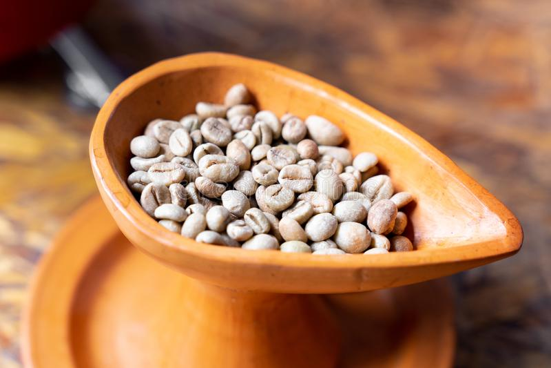 κλείστε επάνω το ακατέργαστο πράσινο φασόλι καφέ στο φλυτζάνι αγγειοπλαστικής στοκ φωτογραφία