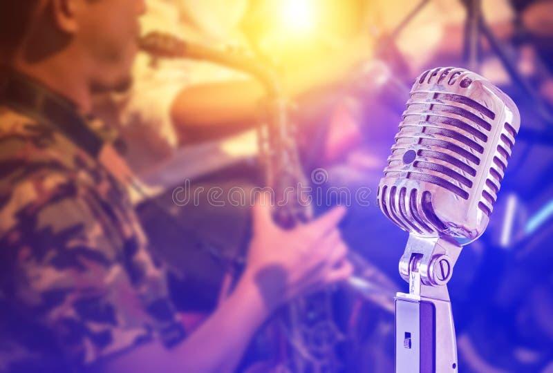 Κλείστε επάνω το αναδρομικό μικρόφωνο με το saxophone παιχνιδιού μουσικών στη ζώνη συμφωνεί κοντά το υπόβαθρο στοκ εικόνα