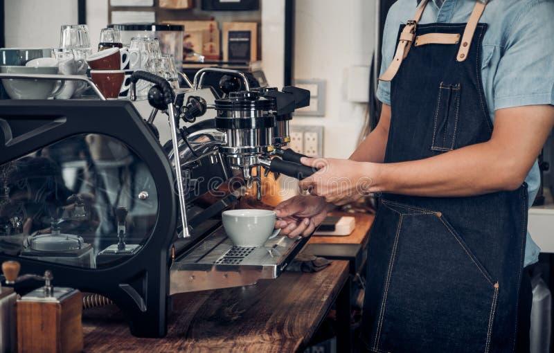 Κλείστε επάνω το αρσενικό barista κατασκευάζοντας τον καυτό καφέ με τη μηχανή στο μετρητή στοκ εικόνες με δικαίωμα ελεύθερης χρήσης