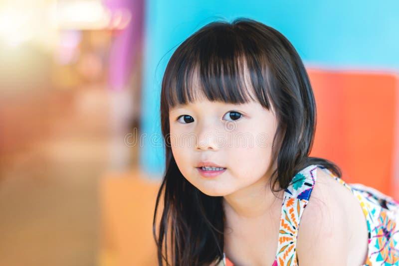 Κλείστε επάνω το ασιατικό μικρό κορίτσι που εξετάζει τη κάμερα, παίζει στην παιδική χαρά στοκ εικόνα με δικαίωμα ελεύθερης χρήσης